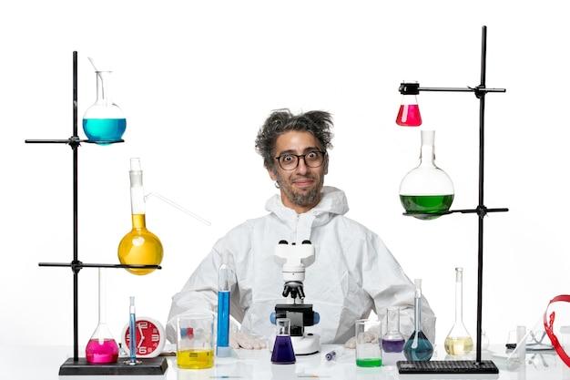Cientista louco de visão frontal em traje de proteção especial sentado ao redor da mesa com soluções sobre vírus da ciência covid de doença de laboratório de chão branco