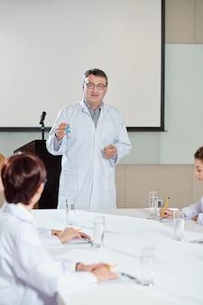 Cientista maduro mostrando frasco com vacina contra coronavírus ao conversar com colegas em conferência médica
