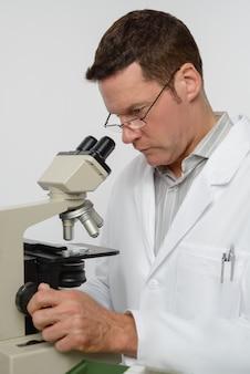 Cientista maduro trabalha em um microscópio