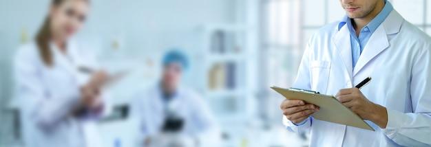Cientista masculina escreve uma nota curta e trabalhando em laboratório com equipe