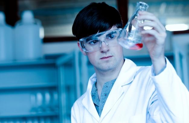 Cientista masculina, olhando para um balão de erlenmeyer