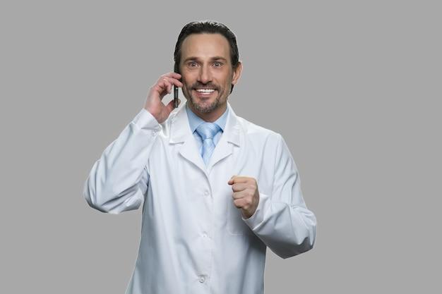 Cientista masculino animado falando no celular. médico entusiasmado ou farmacêutico, gesticulando sucesso em fundo cinza.