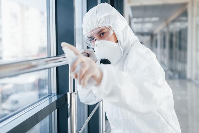 Cientista médica no jaleco, óculos de proteção e máscara em pé dentro de casa com spray antibacteriano