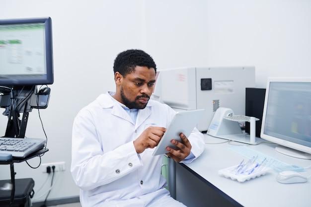 Cientista médico preto, analisando dados sobre tablet