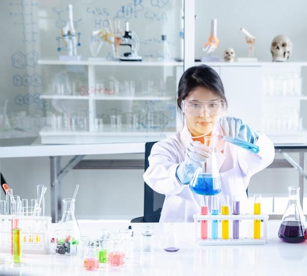 Cientista novo que olha através de um microscópio em um laboratório.