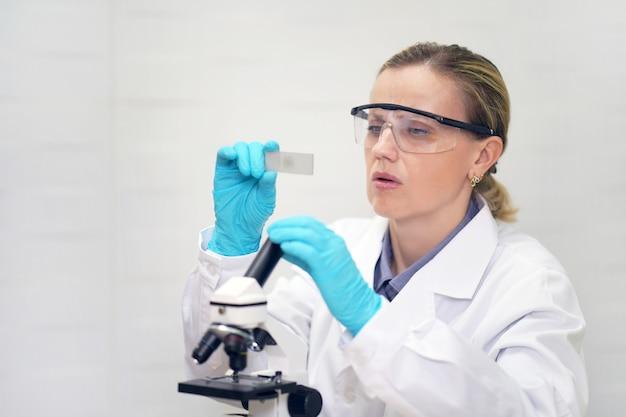 Cientista olha para uma amostra de teste. grave químico feminino está trabalhando em um laboratório. pesquisador cientista usando microscópio no laboratório. bioquímico feminino.