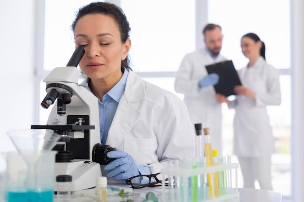 Cientista olhando através do microscópio