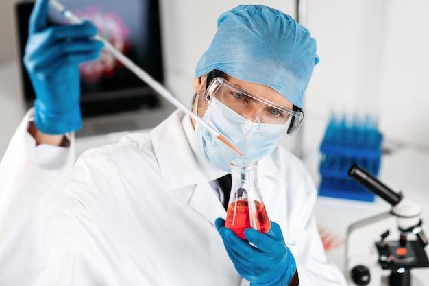 Cientista olhando cuidadosamente para o tubo de ensaio