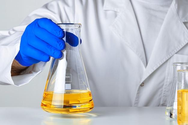 Cientista ou médico em luvas azuis, derramando um pouco de líquido amarelo em um balão