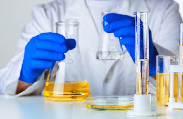 Cientista ou médico em luvas azuis, despejando um líquido amarelo em um balão