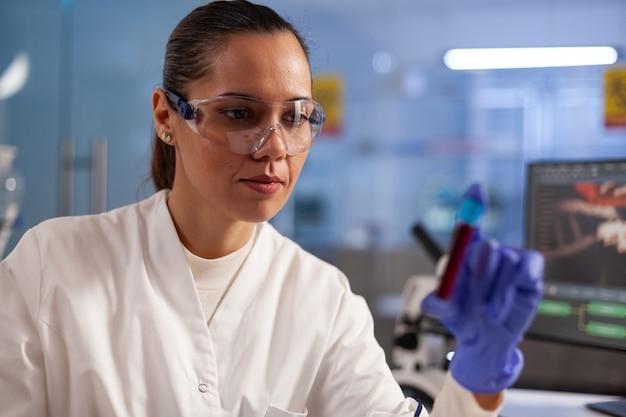 Cientista pesquisador médico analisando amostra de frasco de sangue para teste de desenvolvimento em laboratório químico. mulher profissional com jaleco, óculos e luvas em busca de tratamento para a saúde