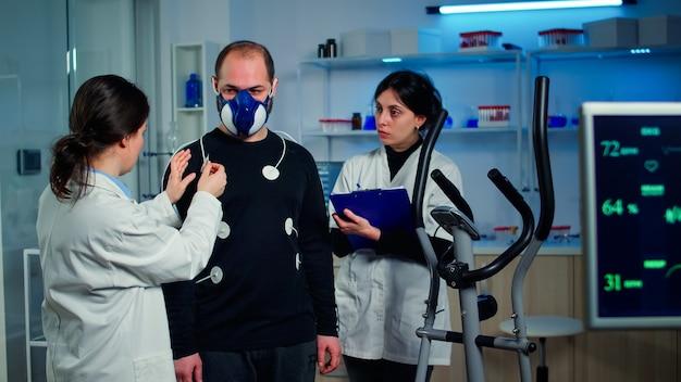 Cientista pesquisador preparando paciente homem para teste de resistência, fixando eletrodos em equipamentos profissionais do corpo