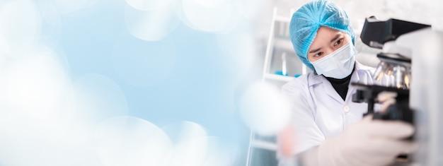 Cientista pesquisador profissional trabalhando para pesquisa de medicina e saúde com microscópio e equipamento de laboratório, tecnologia de biotecnologia e química de vírus de teste médico, banner background copyspace