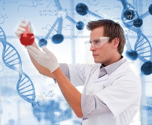 Cientista que olha o vaso de líquido vermelho