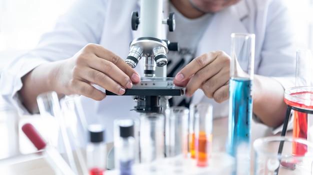 Cientista que usa um microscópio para inspeção do produto