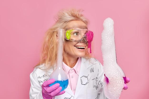 Cientista segura frascos de vidro faz experimento observar a reação com bolhas após a mistura de reagentes feliz após a destilação da solução resultado usa óculos de segurança jaleco branco posa dentro de casa