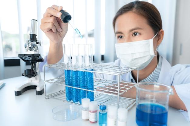 Cientista segurando um conta-gotas para despejar um líquido químico no tubo de ensaio e ver a reação
