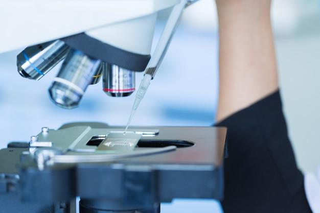 Cientista soltando líquido químico no slide no microscópio, ciência de conceito e tecnologia