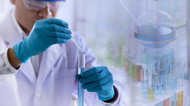 Cientista soltando reagente químico em tubo de ensaio com vidraria
