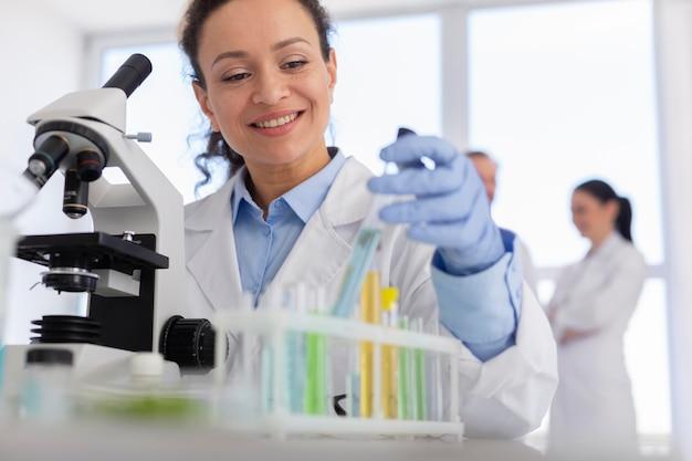 Cientista sorridente com microscópio