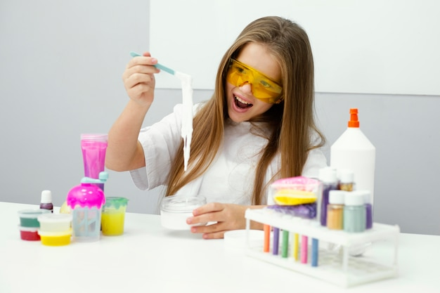 Cientista sorridente se divertindo fazendo limo no laboratório