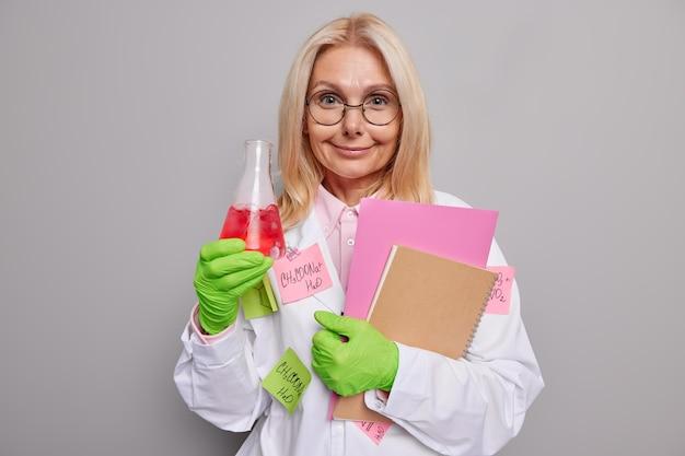 Cientista trabalha em laboratório mostra resultados de experimento químico segura frasco de vidro de cadernos com solidão vermelha usa jaleco médico branco luvas de borracha verdes. ocupação