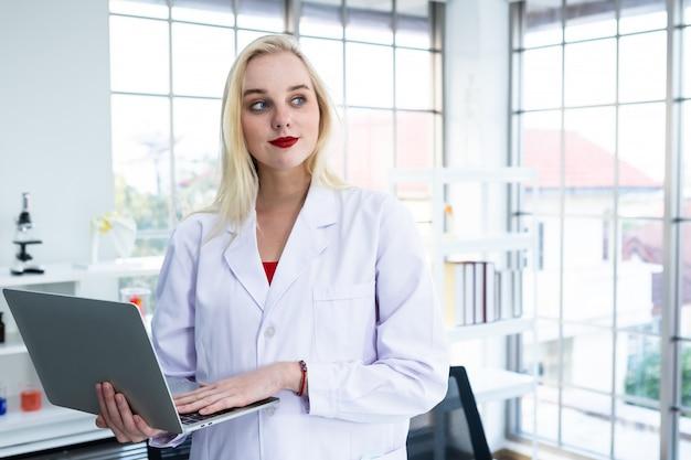 Cientista trabalhando com laptop e pesquisando em um laboratório de química