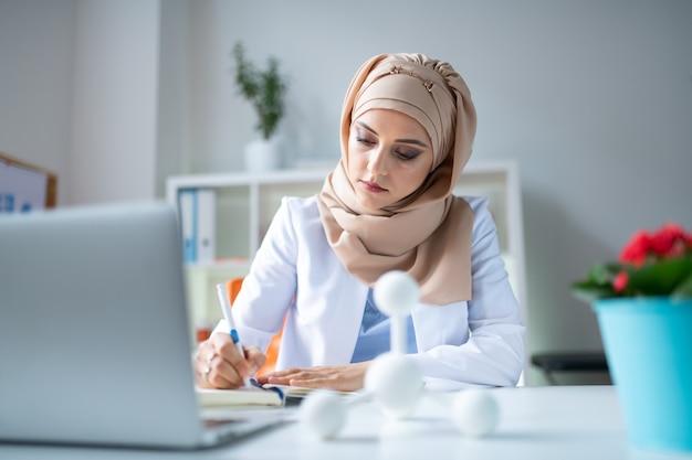 Cientista trabalhando duro. cientista química atraente trabalhando duro enquanto usa o laptop e escreve