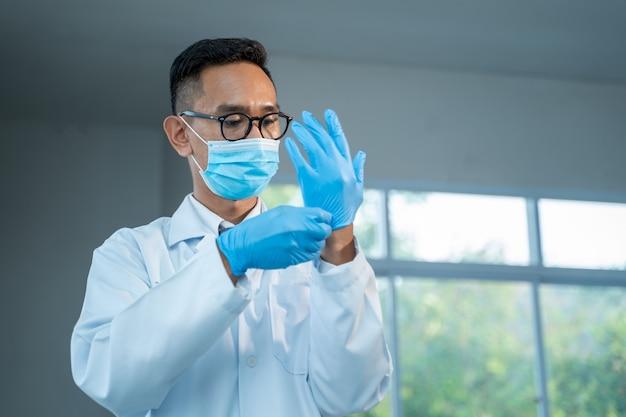 Cientista usando luva., os médicos estão usando luvas de borracha médica para proteção da doença de coronavírus 2019 (covid-19), o coronavírus se transformou em uma emergência global.