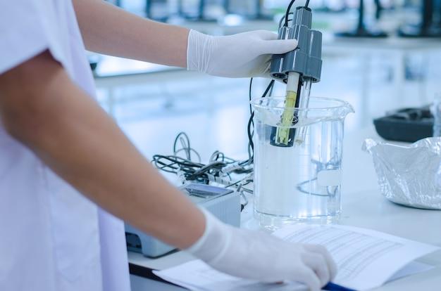 Cientista usou solução química e testes de laboratório para a qualidade da água ou ph meter in laborato
