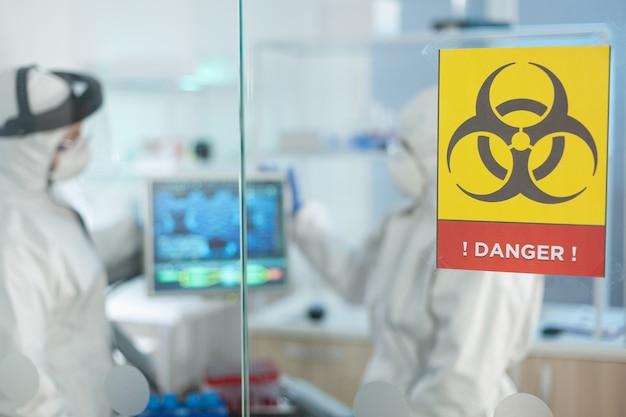 Cientistas biólogos vestindo macacão de proteção médica e trabalhando no laboratório de um hospital microbiológico