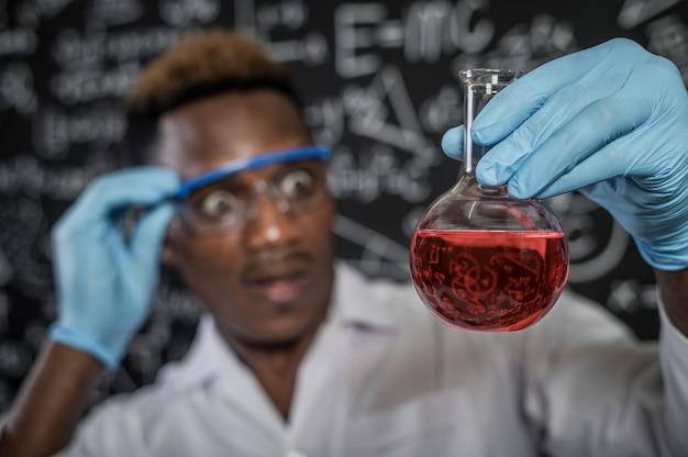 Cientistas chocados com os produtos químicos vermelhos no vidro do laboratório