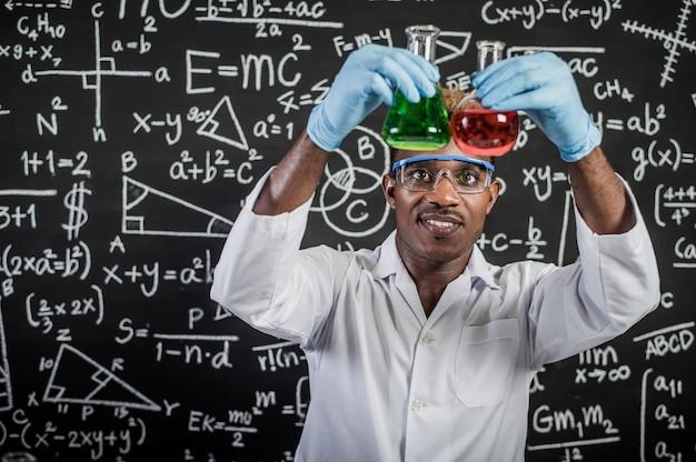 Cientistas examinam os produtos químicos verdes e vermelhos no vidro do laboratório