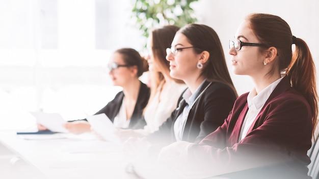 Cientistas femininas no simpósio. mulheres poderosas e inteligentes ouvindo o palestrante na conferência científica.