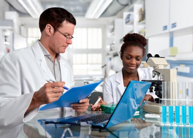Cientistas, homem caucasiano e mulher africana, trabalham em laboratório