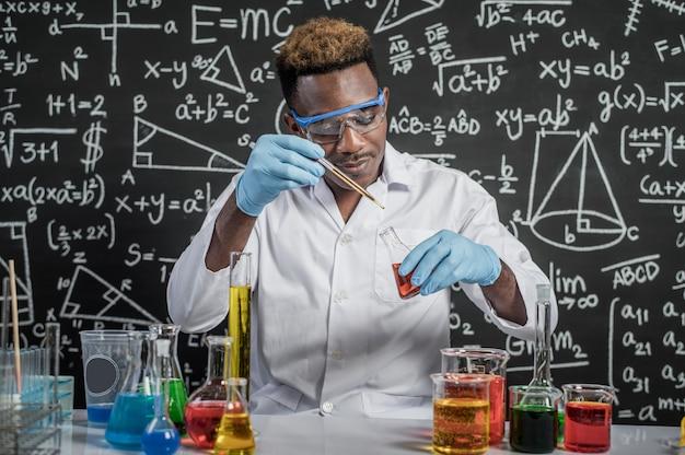 Cientistas jogam produtos químicos amarelos e vermelhos no copo do laboratório