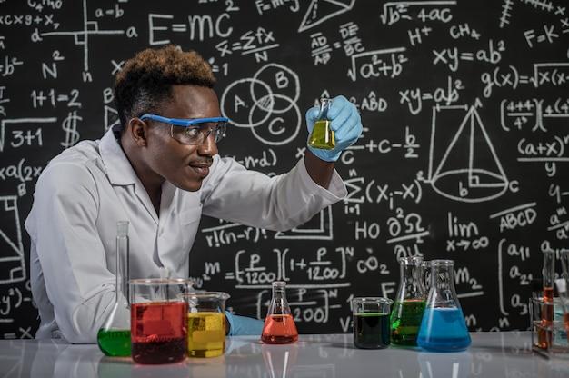 Cientistas olham para os produtos químicos amarelos em vidro no laboratório