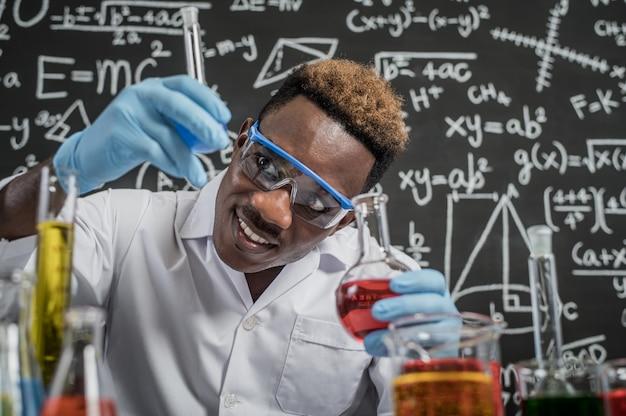 Cientistas olham para os produtos químicos azul-celeste em vidro no laboratório