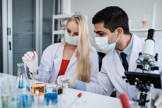Cientistas olhando para um tubo de ensaio com amostra em um cientista de laboratório de química ou jovem