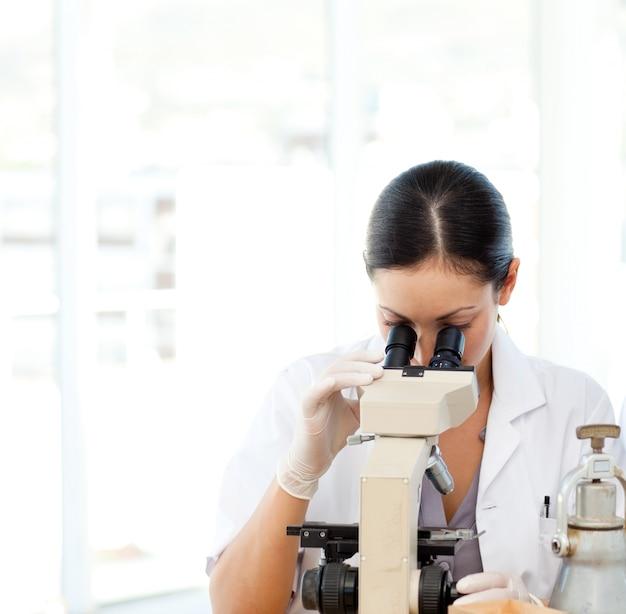 Cientistas que olham através de um microscópio