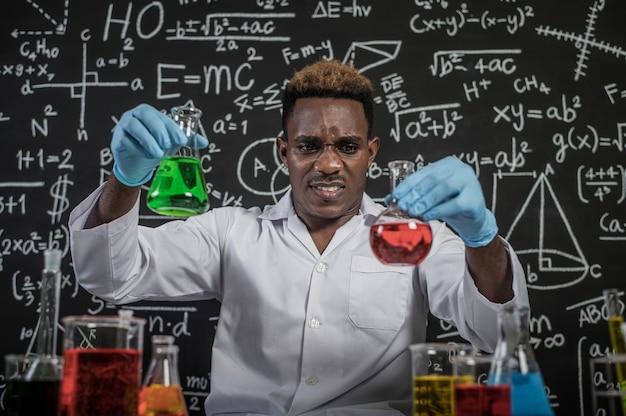 Cientistas seguram copos com produtos químicos verdes e vermelhos e rostos estressados