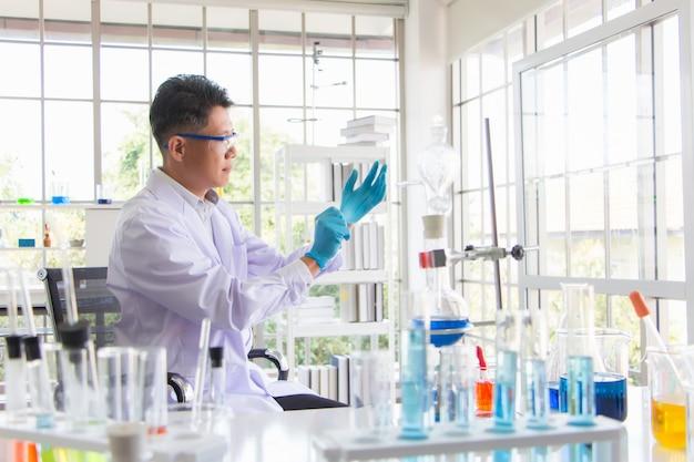 Cientistas seniores, especialistas em química e microbiologia, estão usando luvas e dispositivos de proteção química em um laboratório cheio de dispositivos científicos durante o surto do coronavírus.