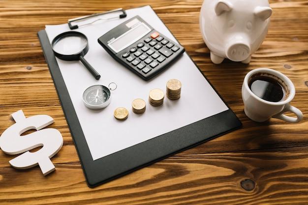 Cifrão; chá preto e piggybank com prancheta no plano de fundo texturizado de madeira