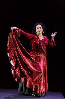 Cigana com cabelo preto encaracolado em um vestido vermelho agita a saia em um fundo preto. foto vertical