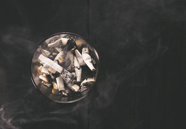 Cigarro com cinzeiro na mesa de madeira. esvazie pronto para sua exposição ou montagem do produto.