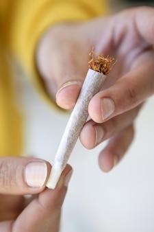 Cigarro comum do tabaco nas mãos apenas preparadas