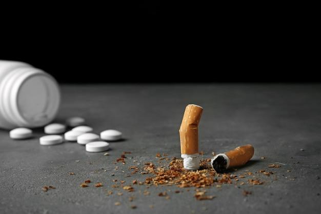 Cigarro danificado e pílulas na mesa cinza