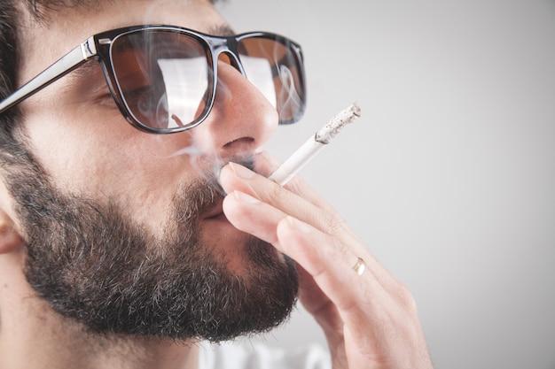 Cigarro de fumo de homem barbudo caucasiano.