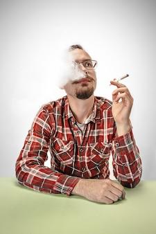 Cigarro de fumo de homem bonito hipster em casa. homem olhando para cima e desfrutando de passar o tempo livre.