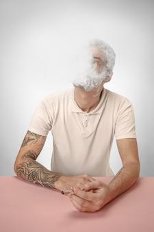 Cigarro de fumo de homem bonito hipster em casa